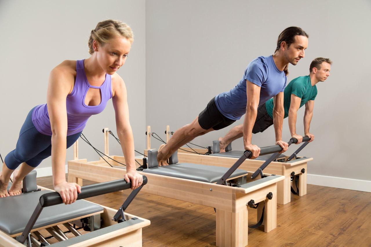 Alunos de Pilates utilizando o equipamento Reformer