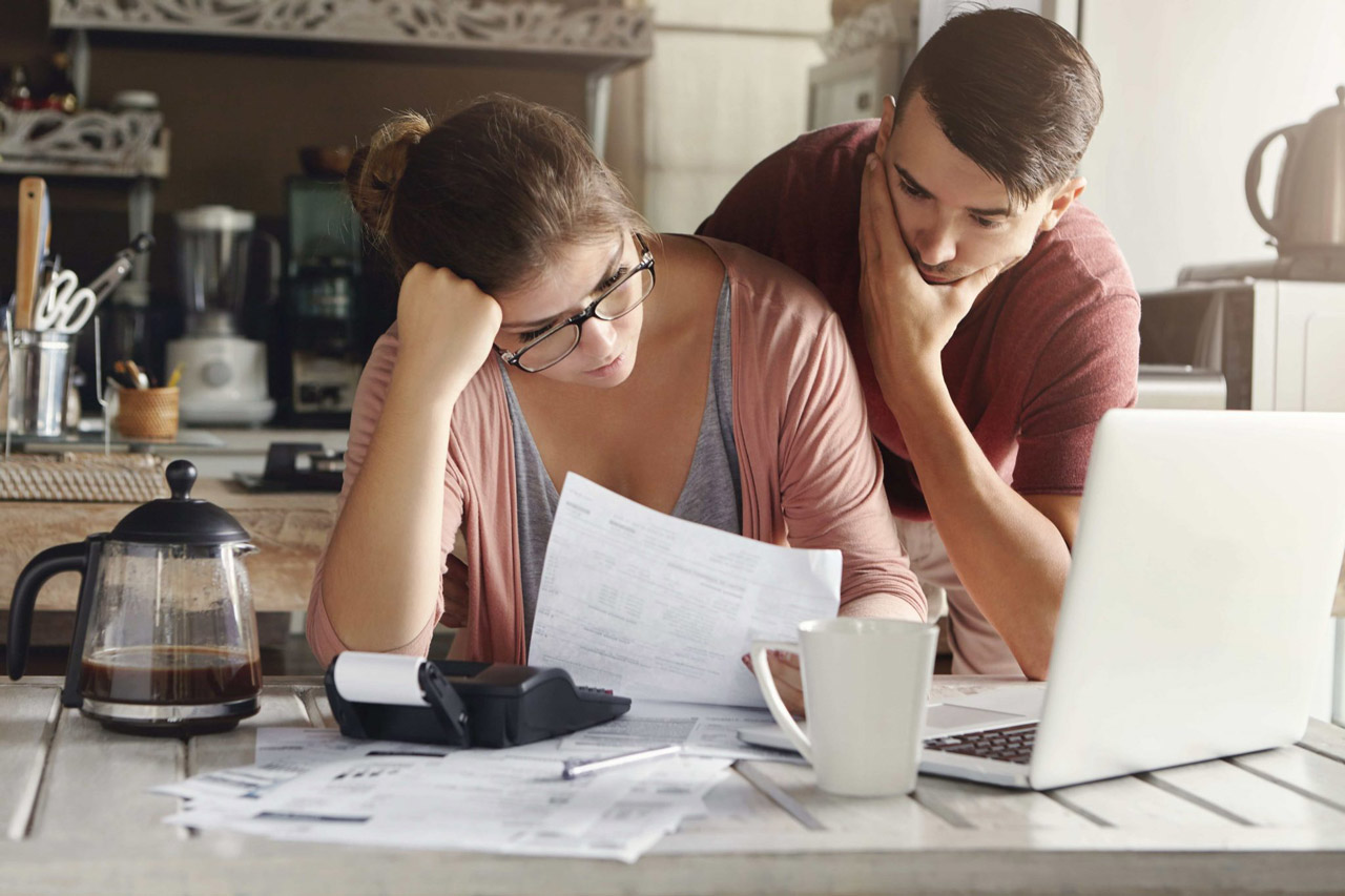 Casal assustado e estressado ao realizar as contas das despesas