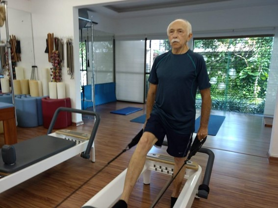 Idoso realizando aula de Pilates