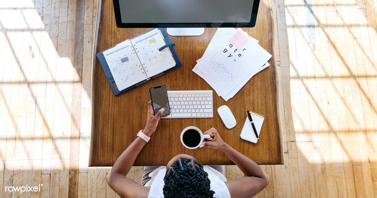 Designer mulher negra tomando café em em sua mesa de trabalho em frente a macbook