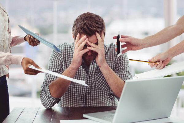 Homem estressado no trabalho ao receber diversas cobranças