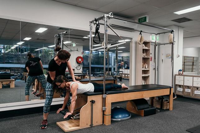 Instrutor auxiliando aluno a utilizar equipamento de pilates