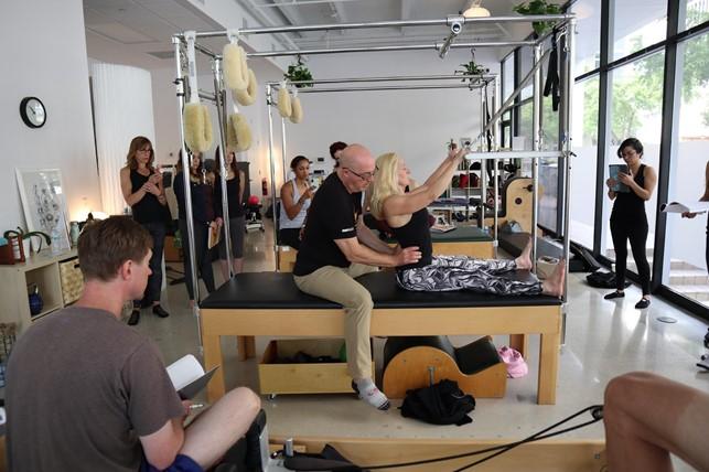 Instrutor de pilates auxiliando aluna no cadillac reformer durante aula para turma