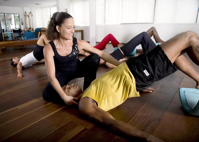 Instrutora de pilates auxiliando aluno na elevação pélvica durante aula para turma