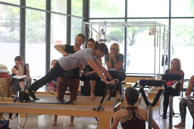 Instrutora de pilates auxiliando aluno no reformer durante aula para turma