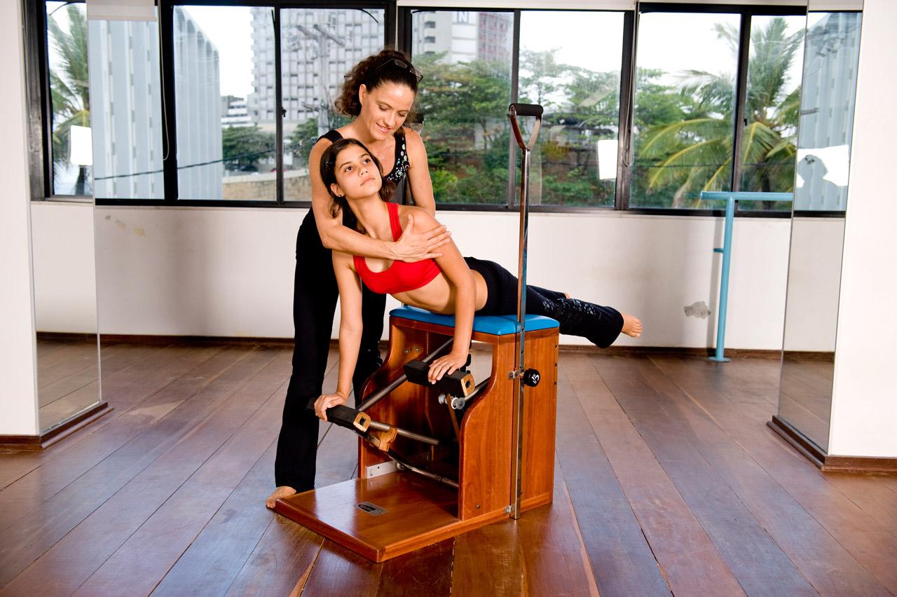 Instrutora auxiliando aluna jovem de Pilates no equipamento STEP CHAIR