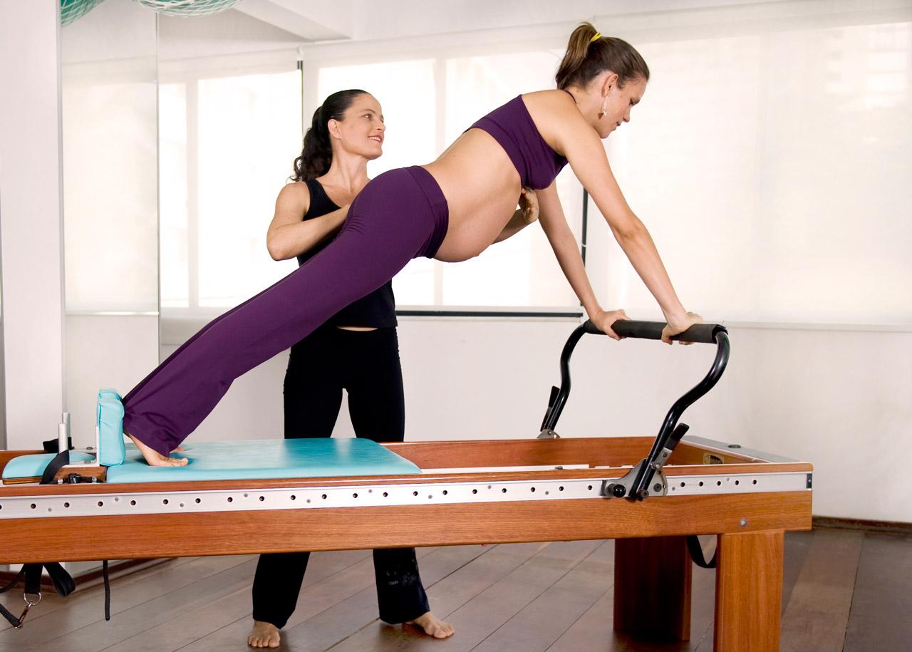 Mulher grávida fazendo Pilates no equipamento Reformer acompanhada de instrutora