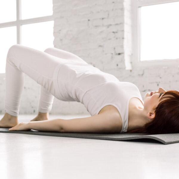 Mulher praticando Pilates realizando elevação pélvica