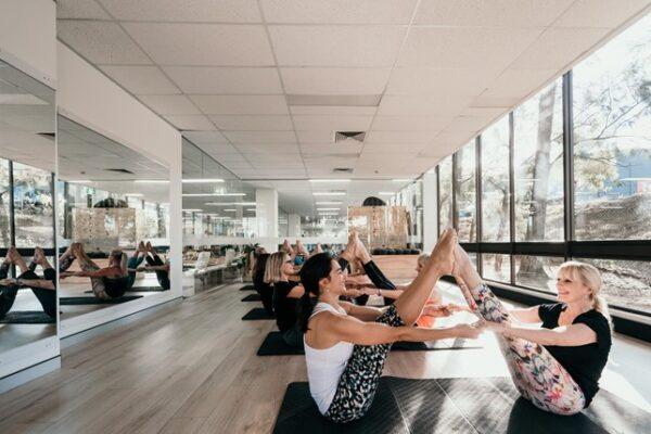 Turma feminina de pilates realizando movimento em dupla