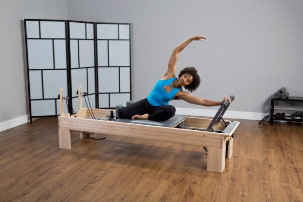 Mulher negra de camisa azul e calça preta utilizando o Reformer para pilates
