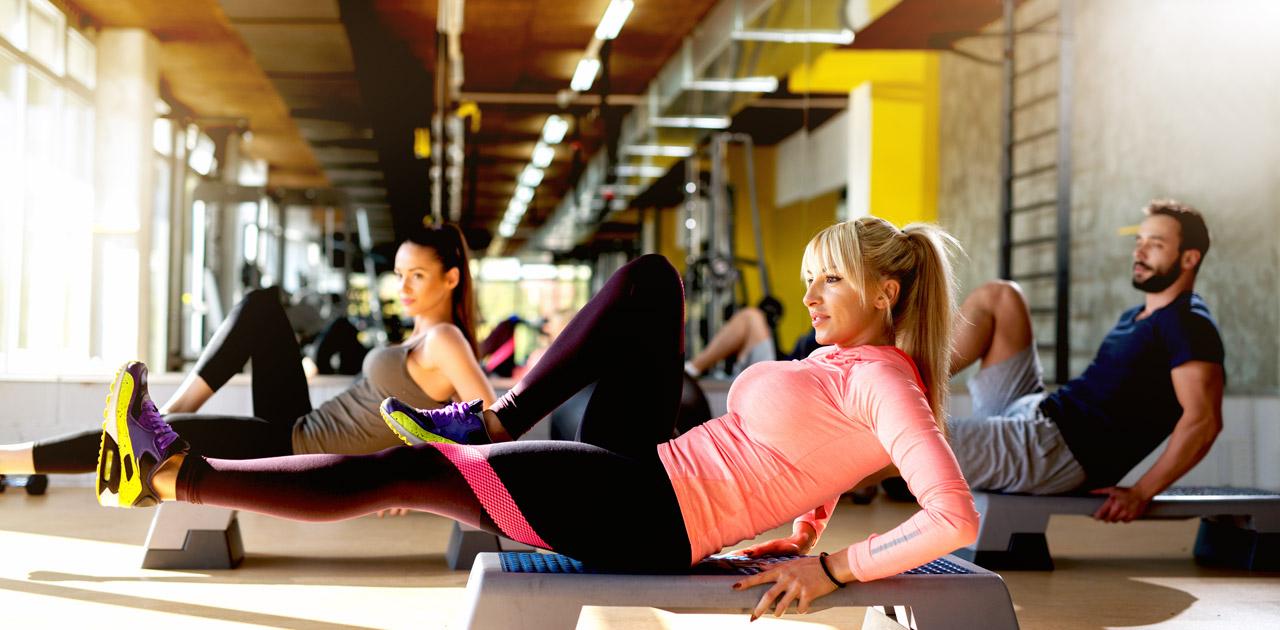 alunos de pilates exercitando abdomen e pernas