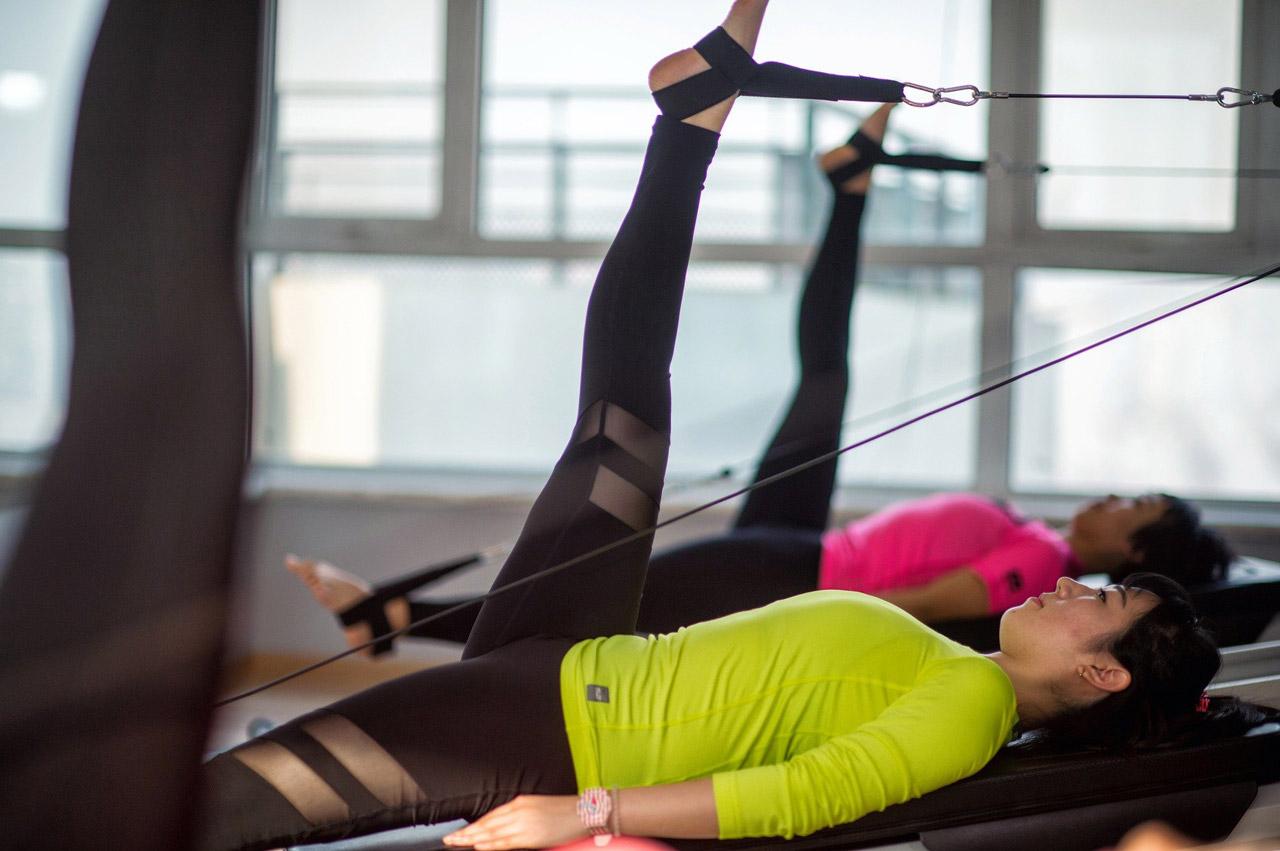 alunos de pilates realizando alongamento de perna com elasticos preso nos pés
