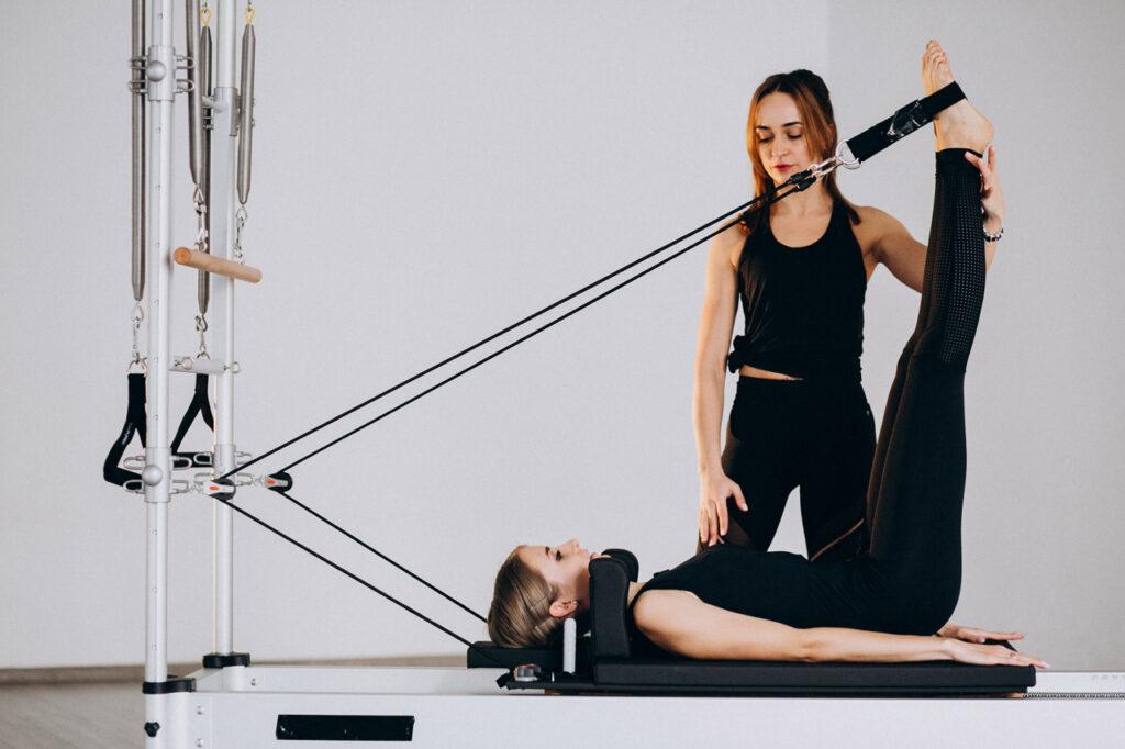 instrutora auxiliando aluna com o equipamento de pilates para reabilitação neurológica