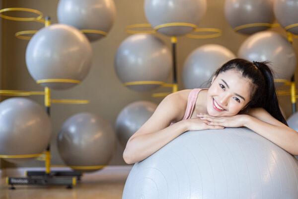 mulher debruçada em bola de pilates sorrindo para a camera