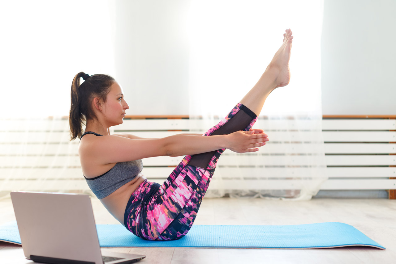 Praticante de pilates realizando movimento abdominal