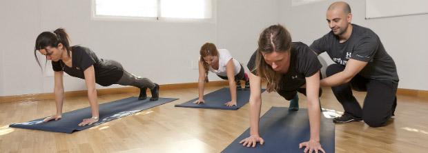 Instrutor de pilates auxiliando turma de alunas