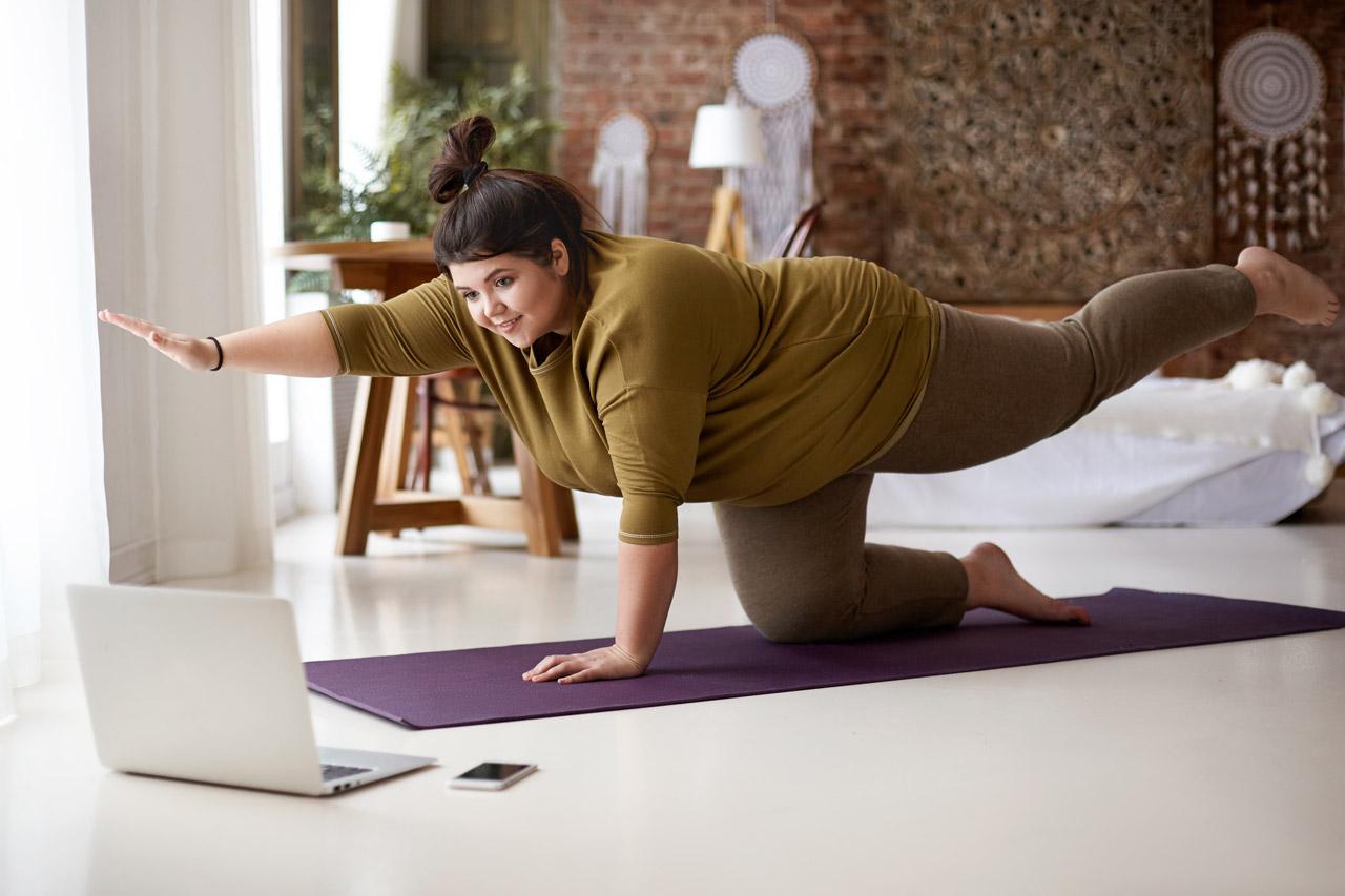 Aluna de pilates realizando alongamento durante aula online